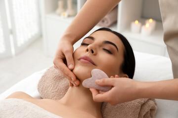 Fototapeta Young woman receiving facial massage with gua sha tool in beauty salon obraz