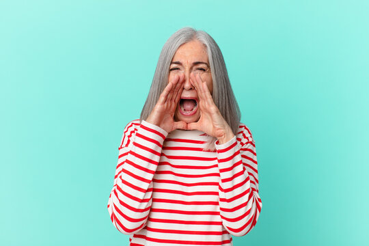 middle age white hair woman feeling happy,giving a big shout out with hands next to mouth