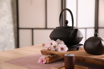 Obraz Beautiful traditional tea ceremony set and sakura flowers on wooden table. Space for text - fototapety do salonu