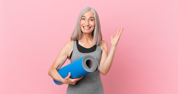 middle age white hair woman feeling happy, surprised realizing a solution or idea and holding a yoga mat. fitness concept
