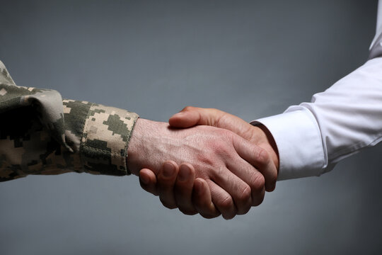 Soldier and businessman shaking hands against grey background, closeup