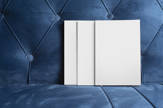 Books with blank cover on a blue velvet sofa, editable mock-up series ready for design