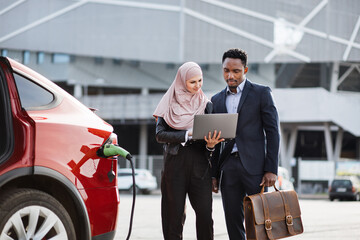 Fototapeta Muslim woman in hijab holding wireless laptop and showing something to african man in business suit. Man and woman standing near electric car that is charging. Concept of auto business. obraz