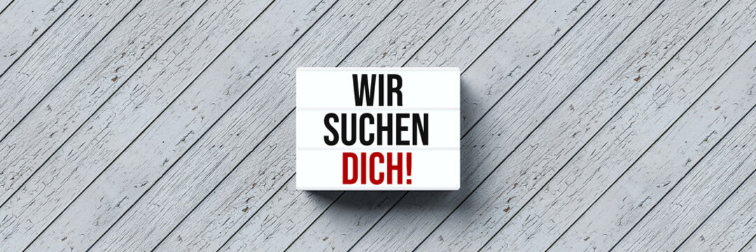 lightbox with German message for WE ARE LOOKING FOR YOU! on wooden background