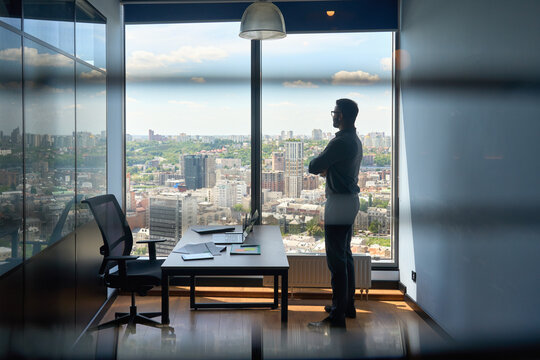 Silhouette of indian confident successful businessman thinking imagining future corporate financial career standing at office near window of high floor building with city view on big urban center.