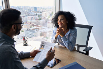 Fototapeta Friendly interview between Indian businessman hr director holding paper cv hiring for job female African American applicant manager sitting in contemporary office. Human resources recruitment concept. obraz