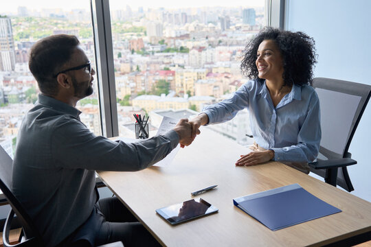 Indian friendly ceo businessman hr director holding job contract hiring welcoming female African American applicant manager shaking hands in contemporary office. Human resources concept.