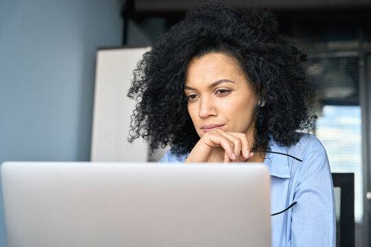 Young serious concerned African American businesswoman sitting at desk looking laptop computer in contemporary corporation office. Business technologies concept. Close up portrait.