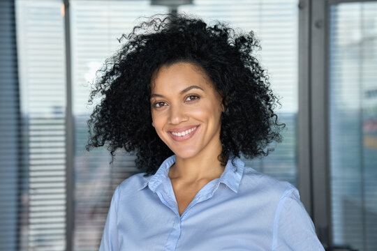 Headshot portrait of confident smiling successful African American businesswoman executive top manager looking at camera posing in modern contemporary corporate office. Business corporate concept.