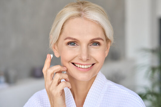 Gorgeous mid age older adult 50 years old blonde woman wears bathrobe in bathroom applying moisturizing sunscreen face skin care cream treatment, looking at camera doing daily beauty routine.