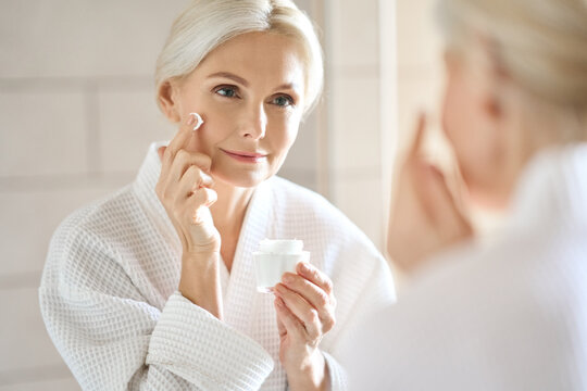 Attractive mid age older adult 50 years old blonde woman wears bathrobe in bathroom applying nourishing antiage face skin care cream treatment, looking at mirror doing daily morning beauty routine.