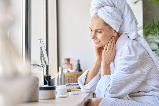 Attractive mid age older adult 50 years old blonde woman wears bathrobe and towel in bathroom touching face, looking at mirror doing daily beauty routine. Skin care treatment concept.