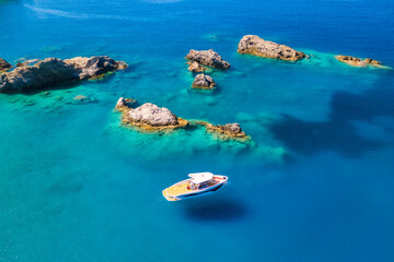 Speed boat on blue sea at sunrise in summer. Aerial view of motorboat on sea bay, rocks in clear azure water. Tropical landscape with yacht, stones. Top view from drone. Travel in Oludeniz, Turkey - fototapety na wymiar