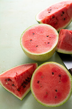 Sliced ripe red watermelon on light green surface