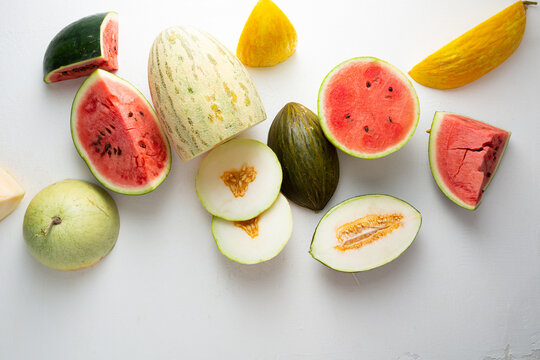 Organic melons and watermelon slice on light surface