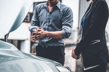 Obraz Man help woman fix the car problem. He pop up the car hood to repair the damaged part. - fototapety do salonu