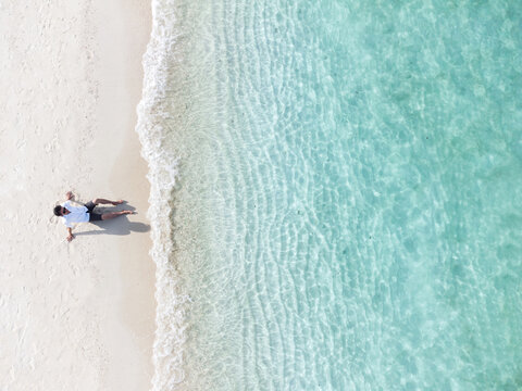 Young man sitting and relaxing at beautiful tropical white sand beach with wave foam and transparent sea, Summer vacation and Travel background Top view from drone