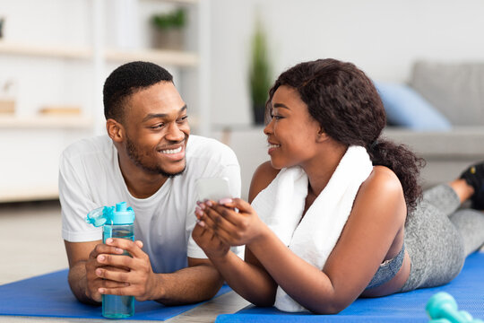 Millennial African American couple lying on sports mats with smartphone after home workout, checking new video online