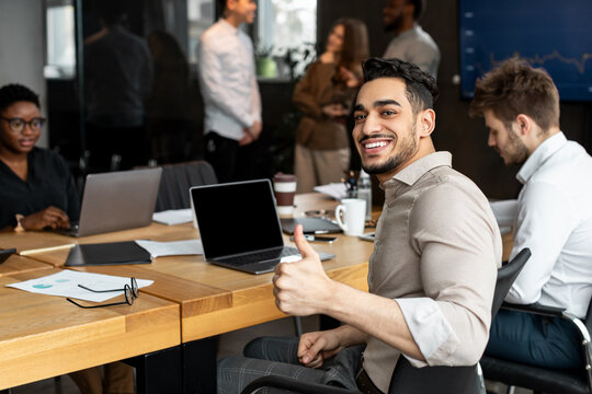 Arab businesman sitting at desk showing thumbs up gesture