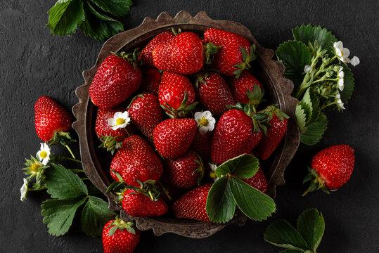 Fresh harvested organic strawberries in metal rustic bowl on black background. top view. healthy tasty food. low key