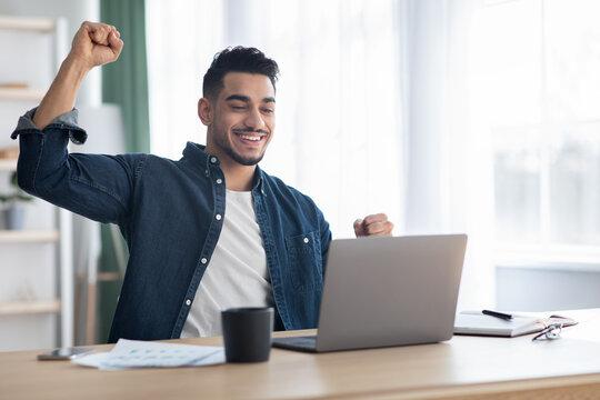 Emotional arab guy freelancer celebrating successful business deal
