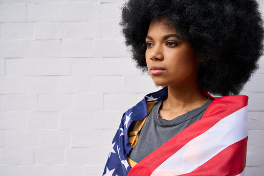 Proud confident patriotic African American gen z girl wrapped in usa flag looking in future with pride standing on white wall background. Equality and freedom in united states concept.