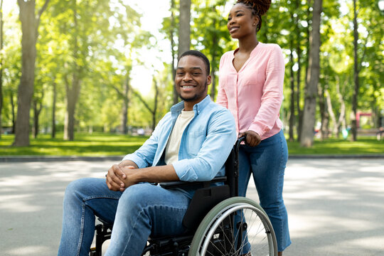 Happy black woman taking her impaired boyfriend in wheelchair for walk at city park