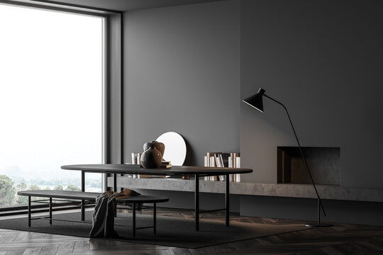 Dark living room interior with table and bench, shelf with books near window
