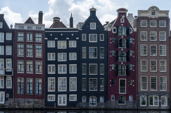 view of the iconic houses on the waterfront at the Damrak in downtown Amsterdam
