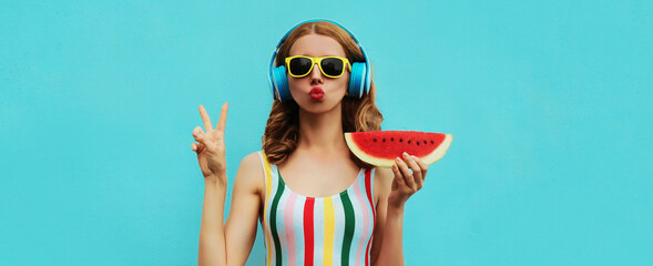 Obraz Summer fashion portrait of young woman in headphones listening to music with juicy slice of watermelon, female model blowing her lips posing on a colorful blue background - fototapety do salonu