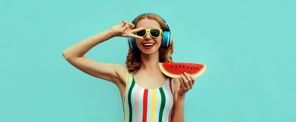 Summer portrait of cheerful happy smiling young woman in headphones listening to music with juicy...