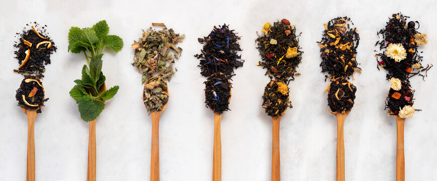 Large assortment of dry tea in spoons from herbs, flowers, berries and fruits on on  stone marble countertop.