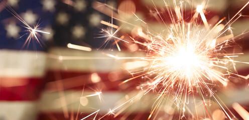Fototapeta Sparks flying off a burning sparkler in front of the US American flag for patriotic 4th of July celebration. obraz