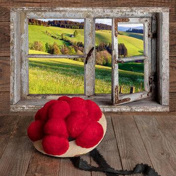 Blick durch ein Fenster mit Bollenhut auf Holztisch