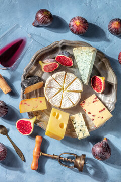 Cheese tasting with red wine and fruit, shot from the top. A delicious cheese platter with Brie, blue cheese and many others