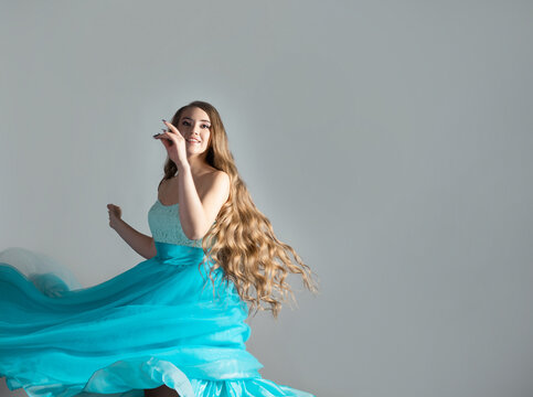 wonderful dancing princess in a lush blue dress, a young beautiful blonde
