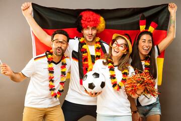 Obraz Gruppe glücklicher Fußballfans aus Deutschland feiern gemeinsam einen Meisterschaft Sieg. - fototapety do salonu