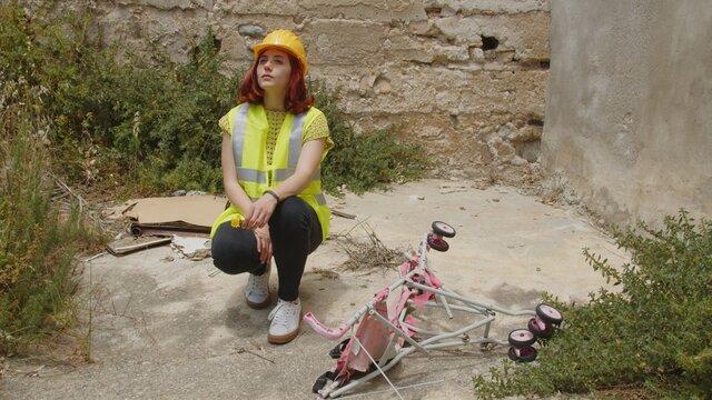 Giovane ragazza soccorritore con caschetto giallo e gilet catarifrangente giunge al disastro