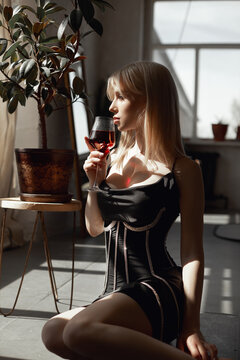 Retro portrait sexy blonde woman with wine glass in black dress, vintage interior woman posing at window. Sensual romantic look, girl relaxes at home