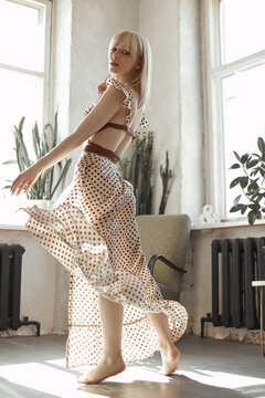 Blonde woman dance in long dress, vintage interior woman posing at window. Sensual romantic retro look, girl relaxes at home