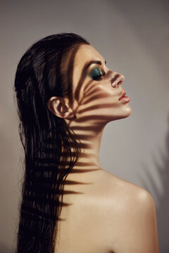 Shadow of palm leaves on girl face. Beautiful makeup. Tropical portrait sexy woman in leaves palm tree. Bright green makeup