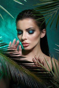 Tropical portrait sexy woman in leaves palm tree. Bright green makeup, shadow of palm leaves on girl face. Beautiful makeup