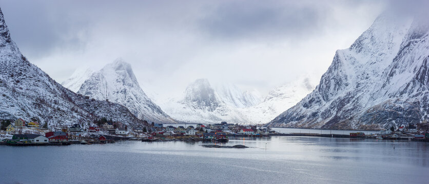 Winter landscape in north Norway: fjord with the little village of Reine against snow covered mountains
