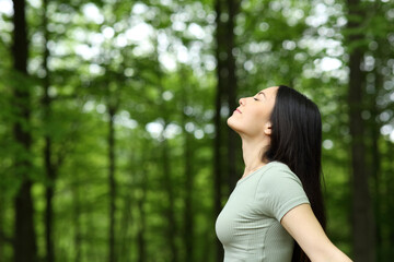 Obraz Asian woman breathing fresh air in a forest - fototapety do salonu