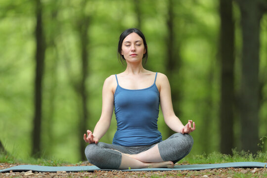 Asian woman doing yoga lotus pose in a forest