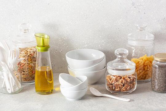 kitchen utensils on modern simple counter, kitchenware jars with dry ingredients bowls