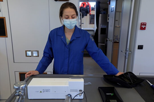 Emily Funk, an associate specialist at the University of California Davis, waits for a fluorescent reader to finish running a SHERLOCK test, on a research vessel on the San Joaquin River off Antioch