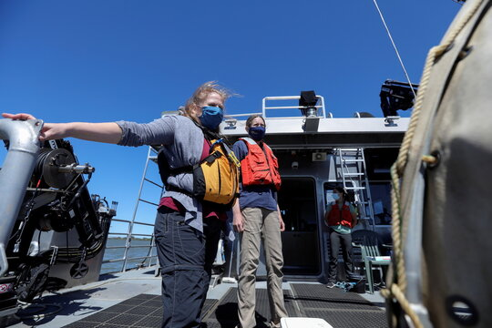 Researchers Melinda Baerwald and Andrea Schreier stand at the stern of a research vessel on the San Joaquin River off Antioch
