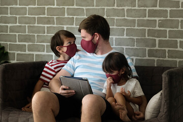 Fototapeta Family Sitting On Sofa, Wearing Mask And Playing Ipad. Happy Family Time obraz