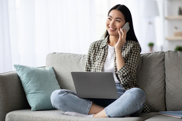 Fototapeta Pretty young woman having phone conversation, using laptop obraz
